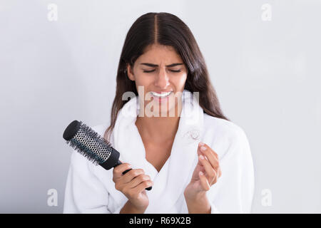Woman In Bathrobe Holding Comb While Looking At Hair Loss - Stock Photo