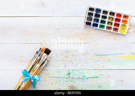 Paint brushes set and box with watercolors on white wooden stained table with splashes, artistic canvas background, tools for creative work, children  - Stock Photo