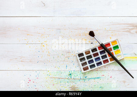 Learning painting concept, paint brush and box with watercolors on white wooden table with splashes, artistic background, creative art workplace for c