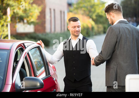 Smiling Valet And Businessperson Standing Near Car - Stock Photo
