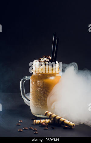 Iced caramel latte coffee in tall glass with syrup and whipped cream. Smoke - Stock Photo
