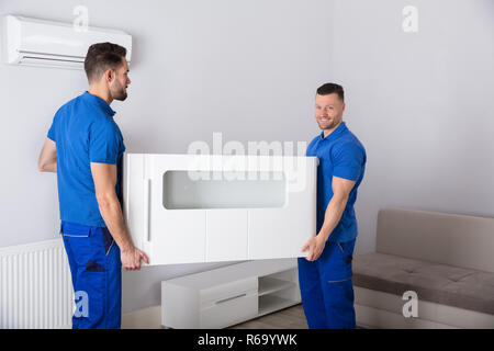 Two Movers Holding Furniture In Living Room - Stock Photo