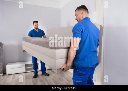Two Men Holding Sofa In Living Room - Stock Photo