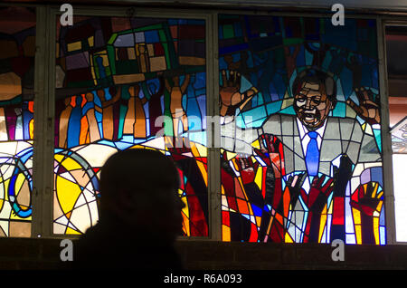 A mourner is seen in front of a stained glass window depicting Nelson Mandela at a church service for the former South African President at Regina Mundi, Soweto, Sunday, December 8, 2013. The elder statesman died Thursday evening, December 5, 2013. PHOTO: EVA-LOTTA JANSSON - Stock Photo