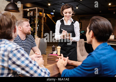 Positive smiling attractive young waitress in black apron standing at guests table and talking to male friends in loft restaurant, serious handsome me - Stock Photo
