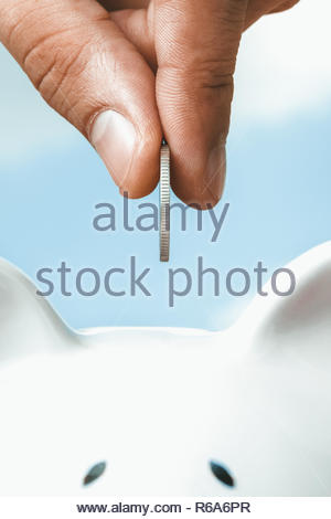 Close up of hand inserting coin in white piggy bank, investment - Stock Photo