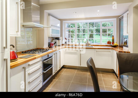 Modular modern kitchen interior with white units and contemporary dining area - Stock Photo