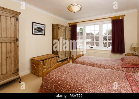 Bedroom with wooden furniture including antique pine wardrobes - Stock Photo