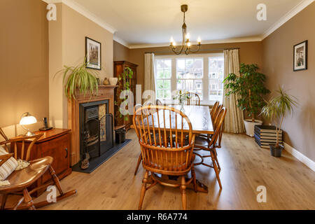 Traditional dining room interior with fireplace, wooden furniture, table and chairs - Stock Photo
