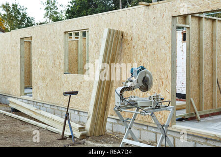 A timber frame house is constructed using OSB sheets to form timber panels. Carpenter's chop saw in the foreground - Stock Photo