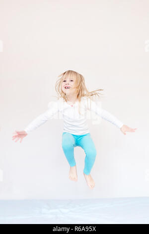 Happy kid jumping over bed. Cute little blond girl having fun indoors. Happy and careless childhood concept - Stock Photo
