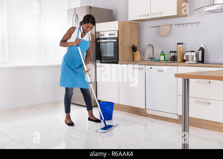 Housewife Cleaning Floor With Mop - Stock Photo