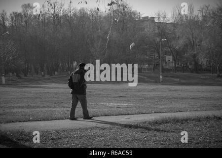 A lonely old man walks on a sunny autumn day. - Stock Photo