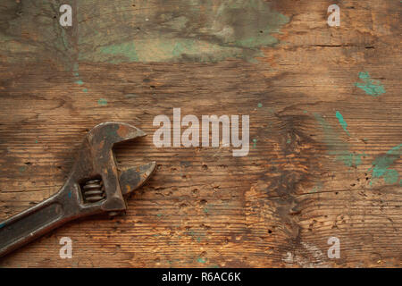 Old rusty adjustable wrench on aged battered wooden table top view. Work concept - Stock Photo