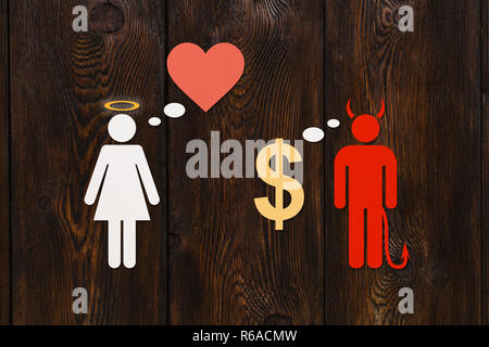 Paper couple, love vs money concept. Devil man and angel woman. Abstract conceptual image - Stock Photo