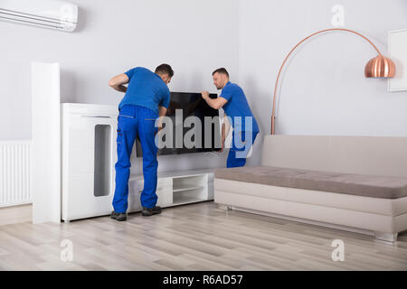 Two Movers Placing Television In Living Room - Stock Photo