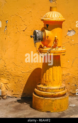 Yellow hydrant in front of the yellow building - Stock Photo