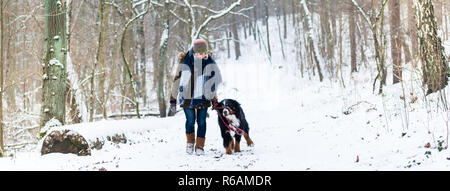 Woman with her dog hiking or walking in winter - Stock Photo