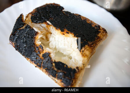 Completely burnt rice on plate next to pot standing on table in kitchen. Concept of unskilled, clumsy chef. Ruined dinner for family - Stock Photo