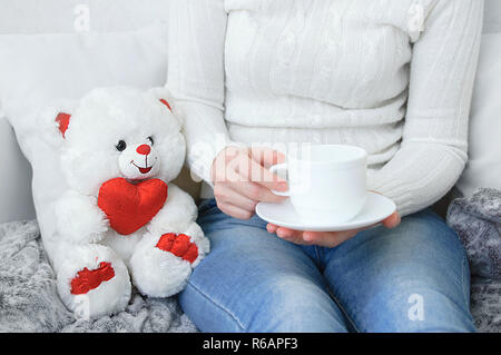 Girl in a white sweater and jeans on the couch with a cup of coffee in their hands. Near white ivy bear. - Stock Photo