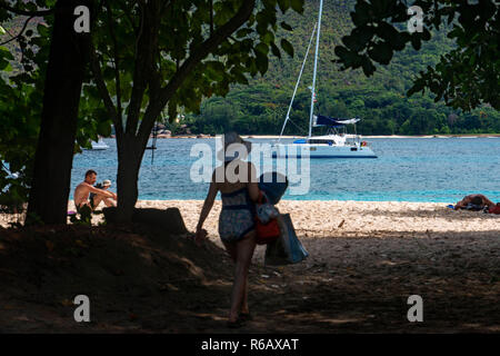 Baie St Anne, beach and boats moored in sheltered harbour, Praslin, Seychelles. - Stock Photo