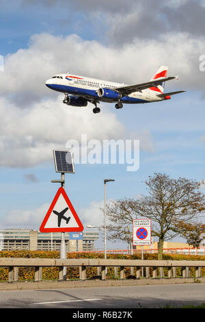 LONDON, ENGLAND - NOVEMBER 2018: Road sign on the A30 road at London Heathrow Airport warning motorists of low flying aircraft. A British Airways jet - Stock Photo