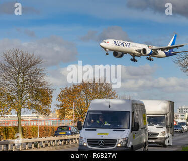 LONDON, ENGLAND - NOVEMBER 2018: Commercial vehicles on the A30 road at London Heathrow Airport with a large passenger jet passing overhead. - Stock Photo