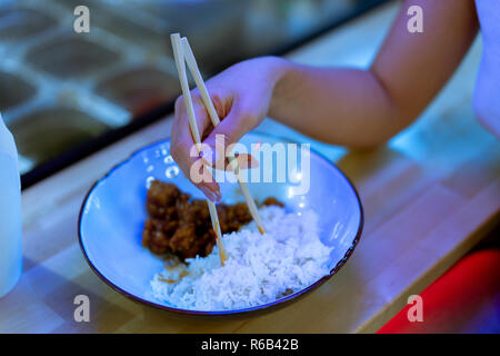 Close up of dish with asian food and hand holding chopsticks. - Stock Photo