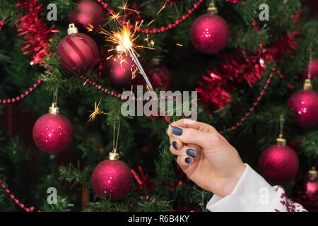 Girl hand holding burning Sparkler blast and Christmas tree with red decoration in background. Christmas and New Year concept. Close up - Stock Photo