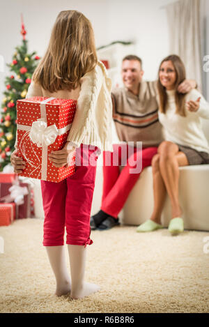 Cute little girl holding gift boxes for surprise her parents for Christmas or New Year. Selective focus. - Stock Photo