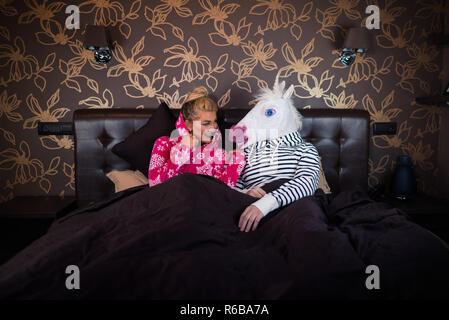 Young woman in pajama sits on bed and talks with funny boyfriend in comical unicorn mask. Unusual couple spends time together in stylish bedroom. - Stock Photo