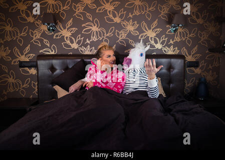 Beautiful young woman in pajama lying on the bed with funny boyfriend in comical mask and dreaming. Unusual couple at the stylish bedroom. - Stock Photo