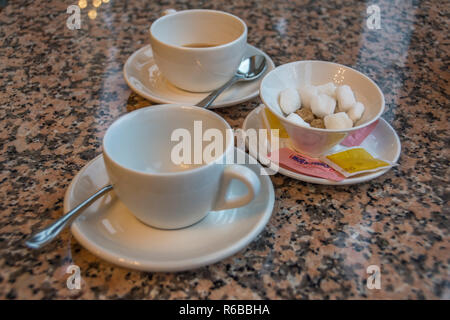 Two white cups of tea on saucers and a sugar bowl with sugar cubes. - Stock Photo