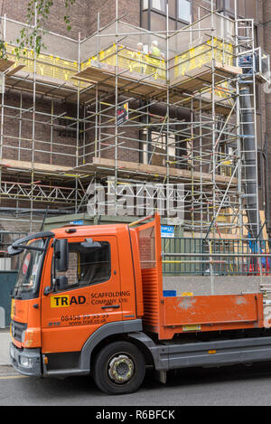 a scaffold on the side of a tall building site with delivery lorry in central London, uk - Stock Photo