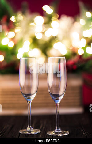 New year holiday or christmas green background. Branches of christmas trees decorated with golden lights, garlands, toys and empty champagne glasses.  - Stock Photo