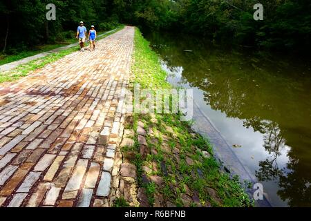 Couple walking along a spillway on the towpath of the Delaware and Raritan Canal, a state park in central New Jersey - Stock Photo