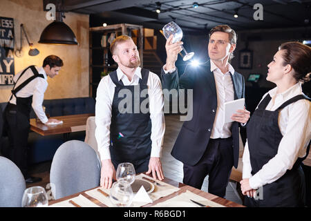 Serious concentrated handsome manager in suit standing at served table and checking wineglass in light while young waiters in aprons serving tables - Stock Photo