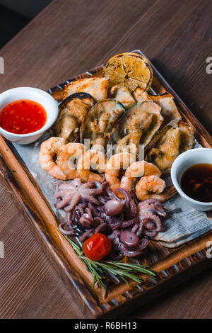 fried seafood squids, shrimps, mussels sauce on wooden board - Stock Photo