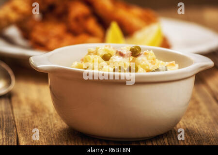 Traditional czech potato salad with mayonnaise and vegetables in white plate - Stock Photo