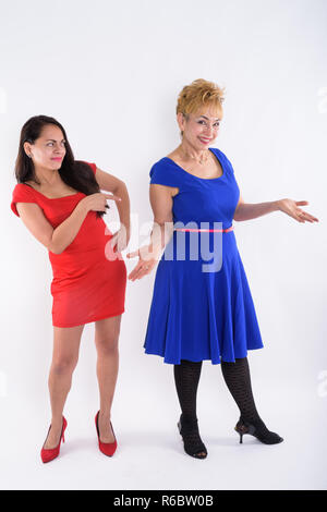 Full body shot of young beautiful woman pointing at happy senior - Stock Photo