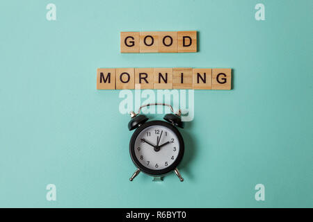 Simply flat lay design alarm clock and Inscription GOOD MORNING letters word on blue pastel colorful trendy background. Breakfast time. Good morning wake up awake concept. Top view copy space - Stock Photo