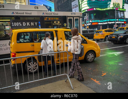 Tourists enter a taxi in Times Square in New York on /Sunday, December 2, 2018.  (© Richard B. Levine) - Stock Photo