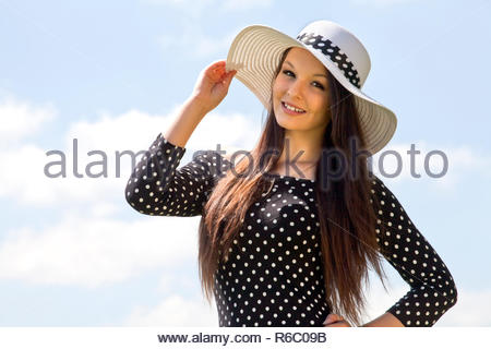 Portrait of young brunette woman in nature against sky. - Stock Photo