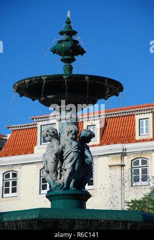 Baroque style bronze fountain on Rossio square in Lisbon, Portugal. Rossio Square is the popular name of the Pedro IV Square - Stock Photo