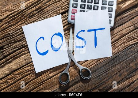 Close-up Of Cost Text On Calculator - Stock Photo