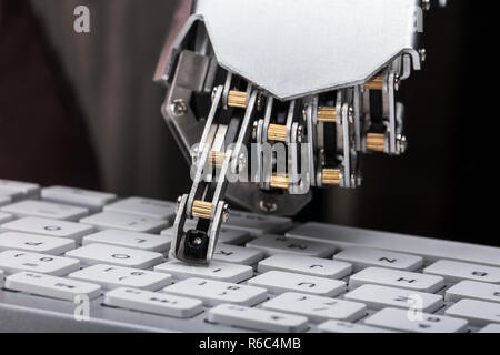 Robotic Hand Typing On Keyboard - Stock Photo