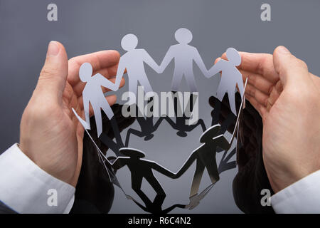 Businessperson's Hand Protecting Cut-out Figures - Stock Photo