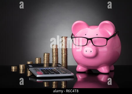 Close-up Of Piggy Bank, Calculator And Stacked Coins - Stock Photo