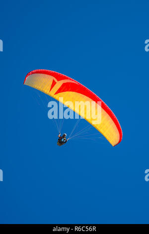 Beautiful yellow and red paraglider flying in blue sky, paste space, smooth background - Stock Photo