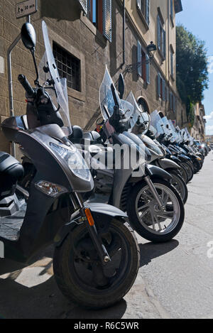 Vertical view of lots of Vespa mopeds parked up on the side of th road in Italy. - Stock Photo
